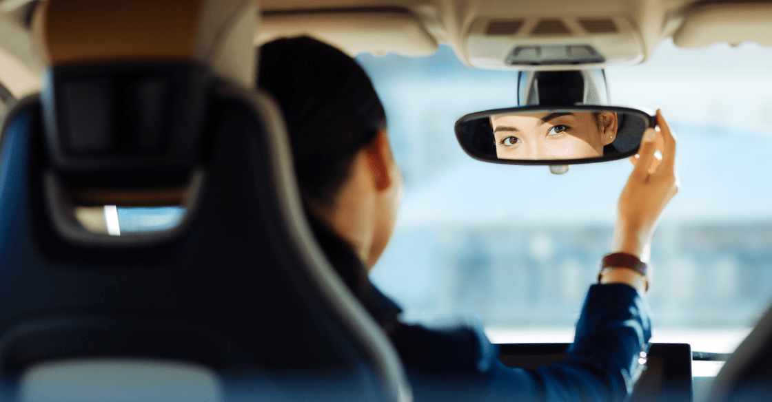 A woman adjusts her rear-mirror in her car as a defensive driving tactic.