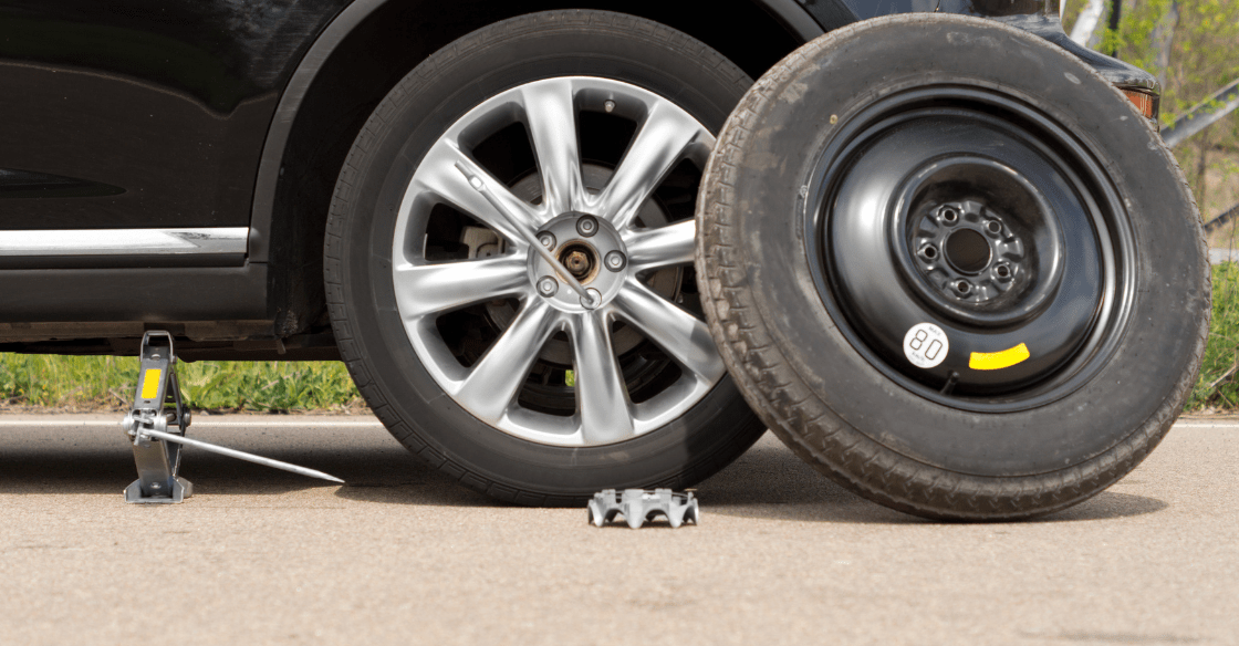 The process of changing a tire using a car jack, lug nut wrench, wheel wedge and a spare tire.