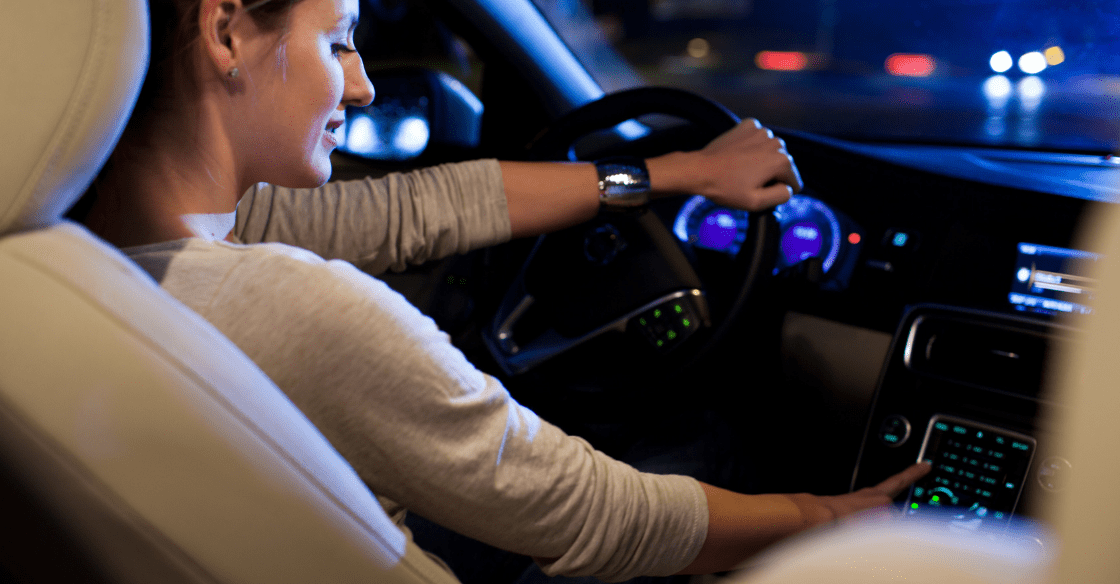 A distracted female driver takes her eyes off the road to adjust her stereo.