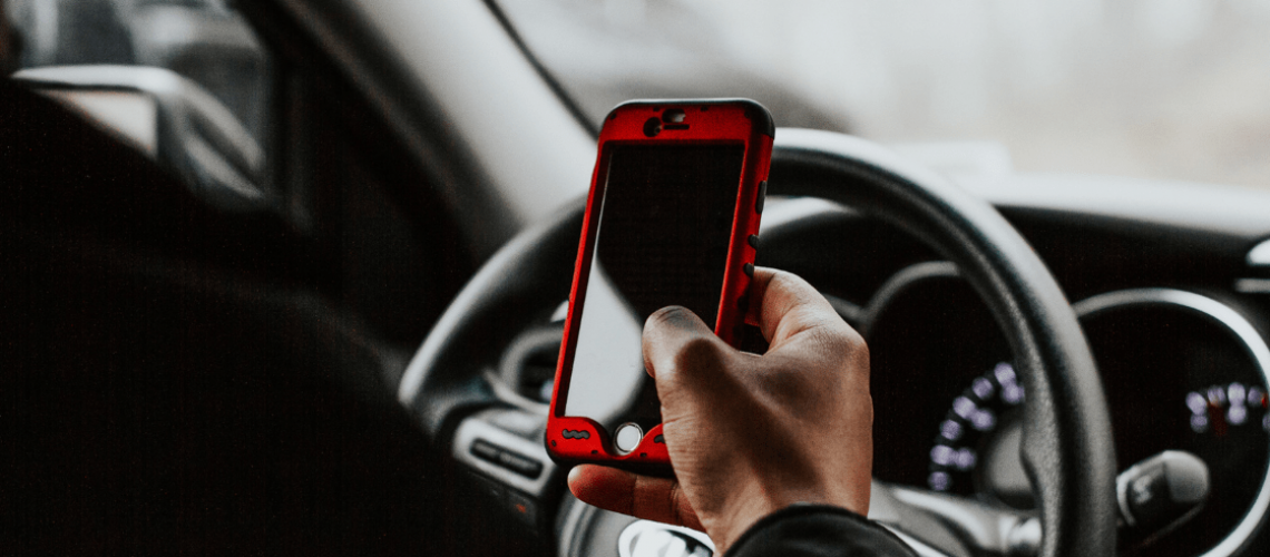 A distracted driver uses his phone while driving.