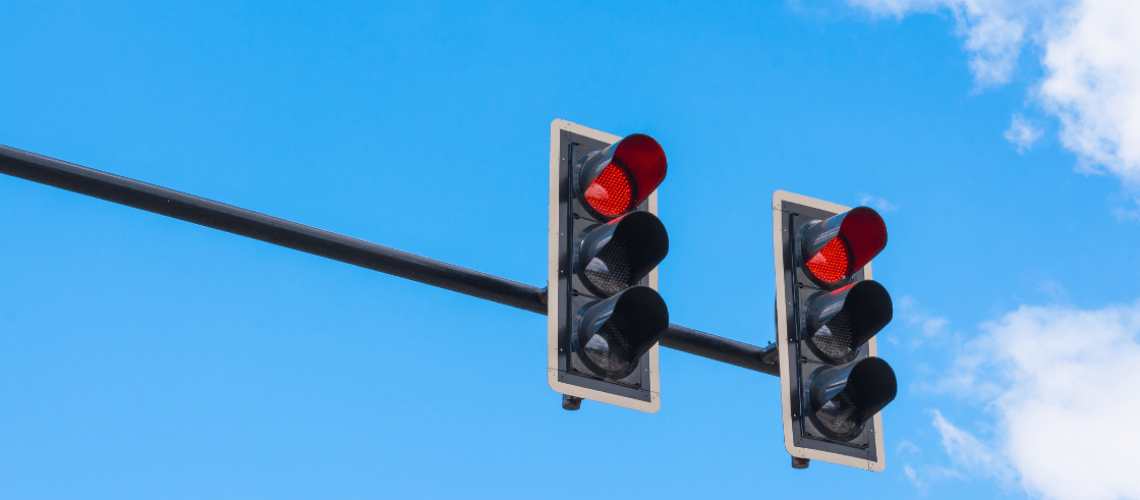 Two red stoplights signaling drivers to stop.