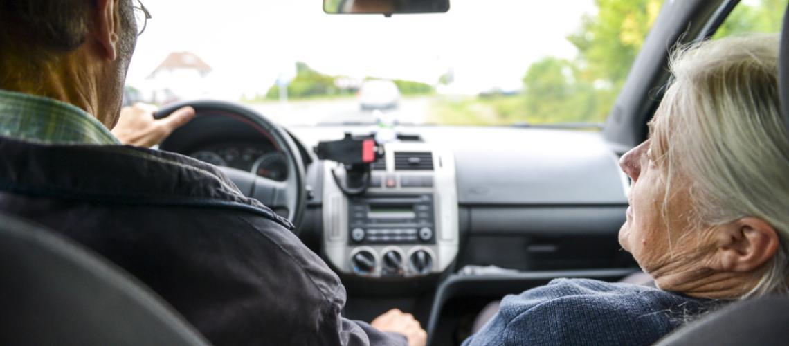Senior citizen couple driving
